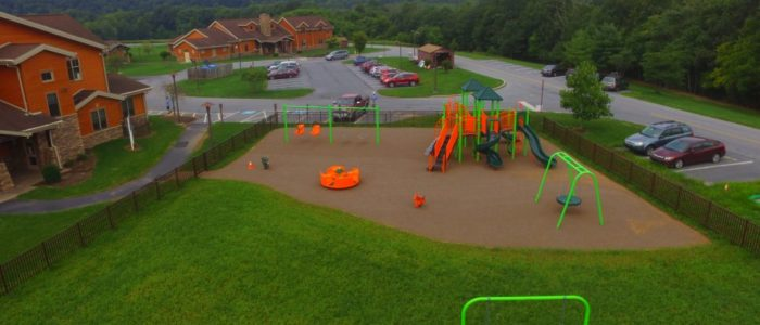 green and orange playground, swing and slides