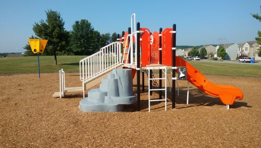 small playground on mulch with climber and orange slide