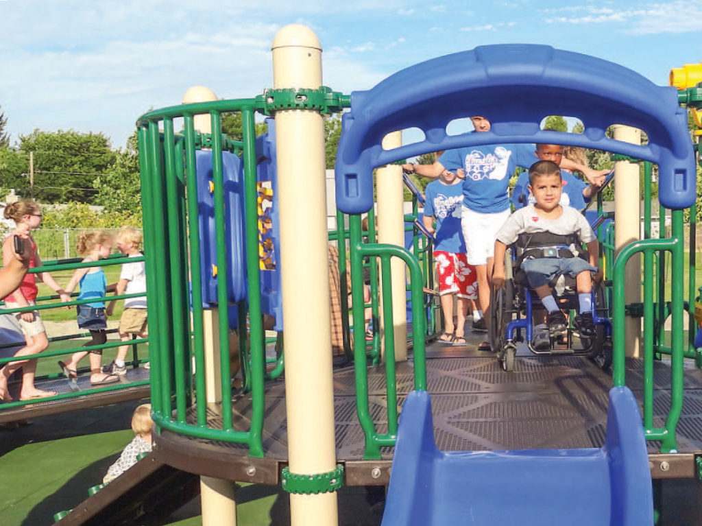 handicapped boy playing on playground with wheelchair