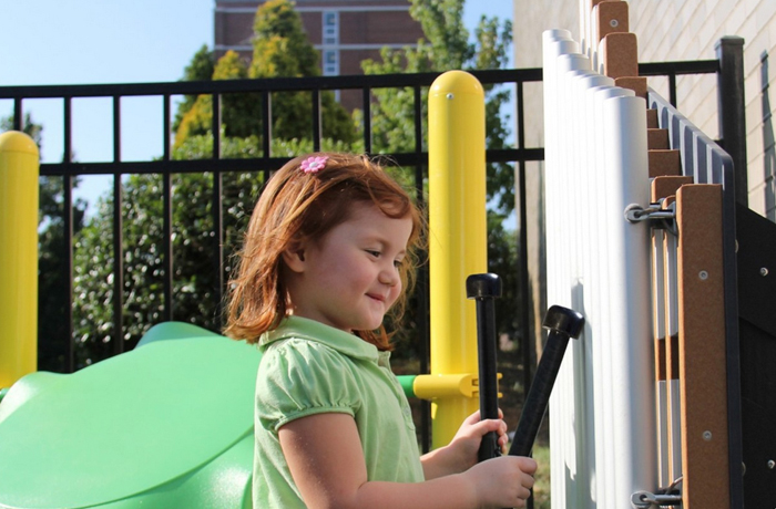 little girl in green shirt playing an instrument on a playground