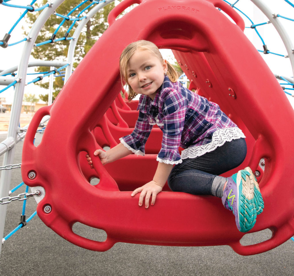 girl climbing on red playground accessory