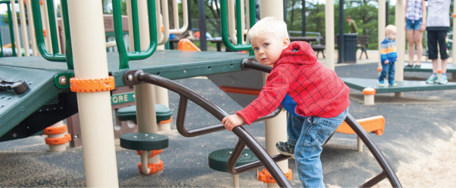 little boy climbing up playground ladder