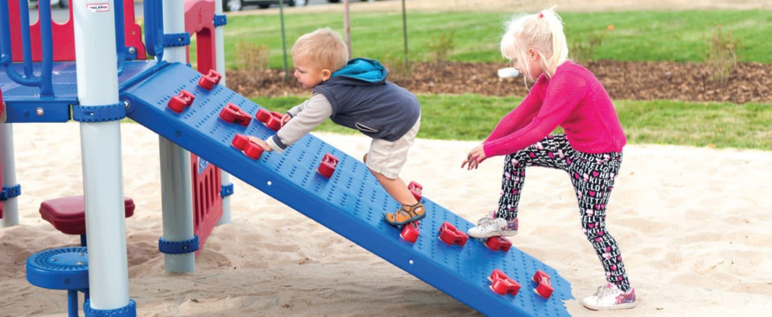 toddler climbing up ramp of playground