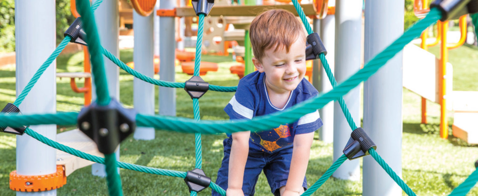 young boy climbing through playground ropes