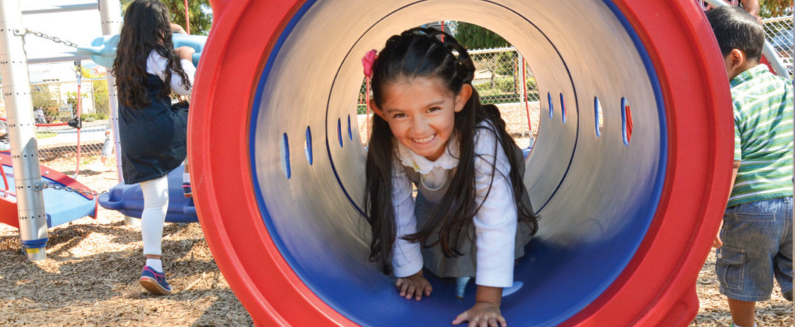 girl climbing through playground tunnel