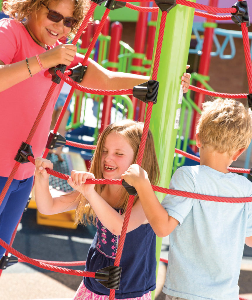 older girl assisting two younger children on playground ropes