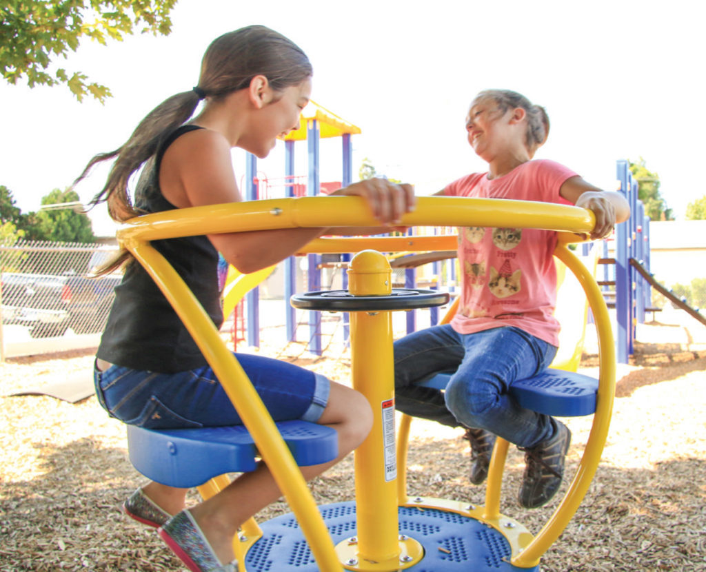 two girls laughing and spinning on playground equipment