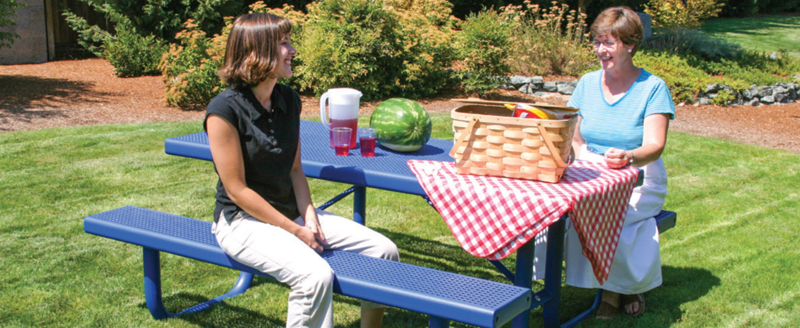 a mother and grandmother having lunch at an outdoor picnic table