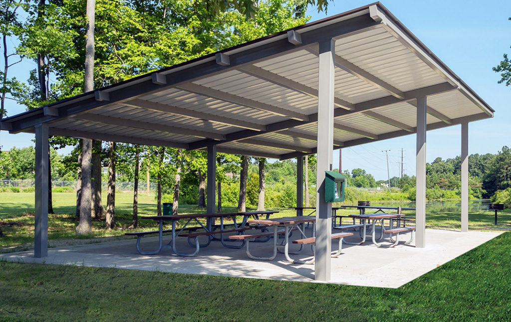 several picnic tables under large roof on cemented slab