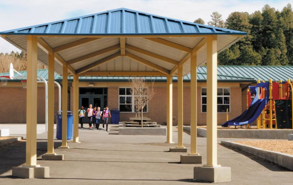 front entry of school with roof over and kids running out