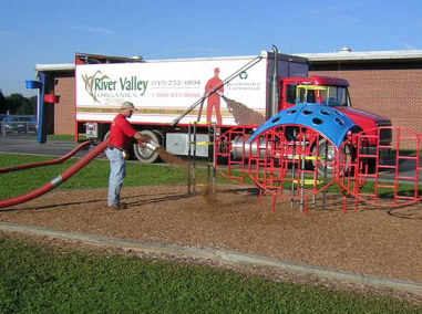 man spraying mulch onto playground floor