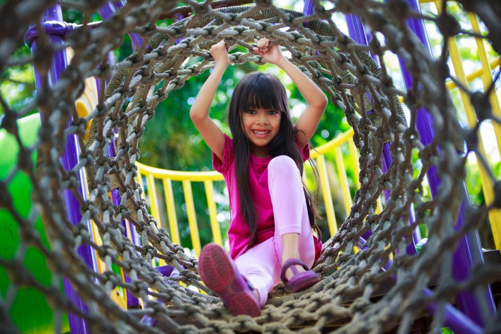 Young girl practicing playground safety on playground equipment